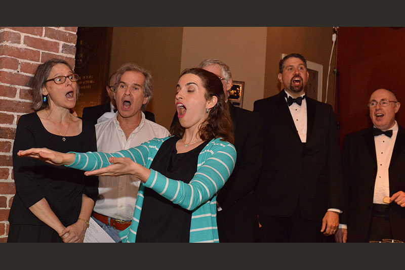 Betty Bauman conducts as Rachel and Michael Miller, Steve Ebstein, Kevin Martin, and Gilbert Schiffer join in singing
